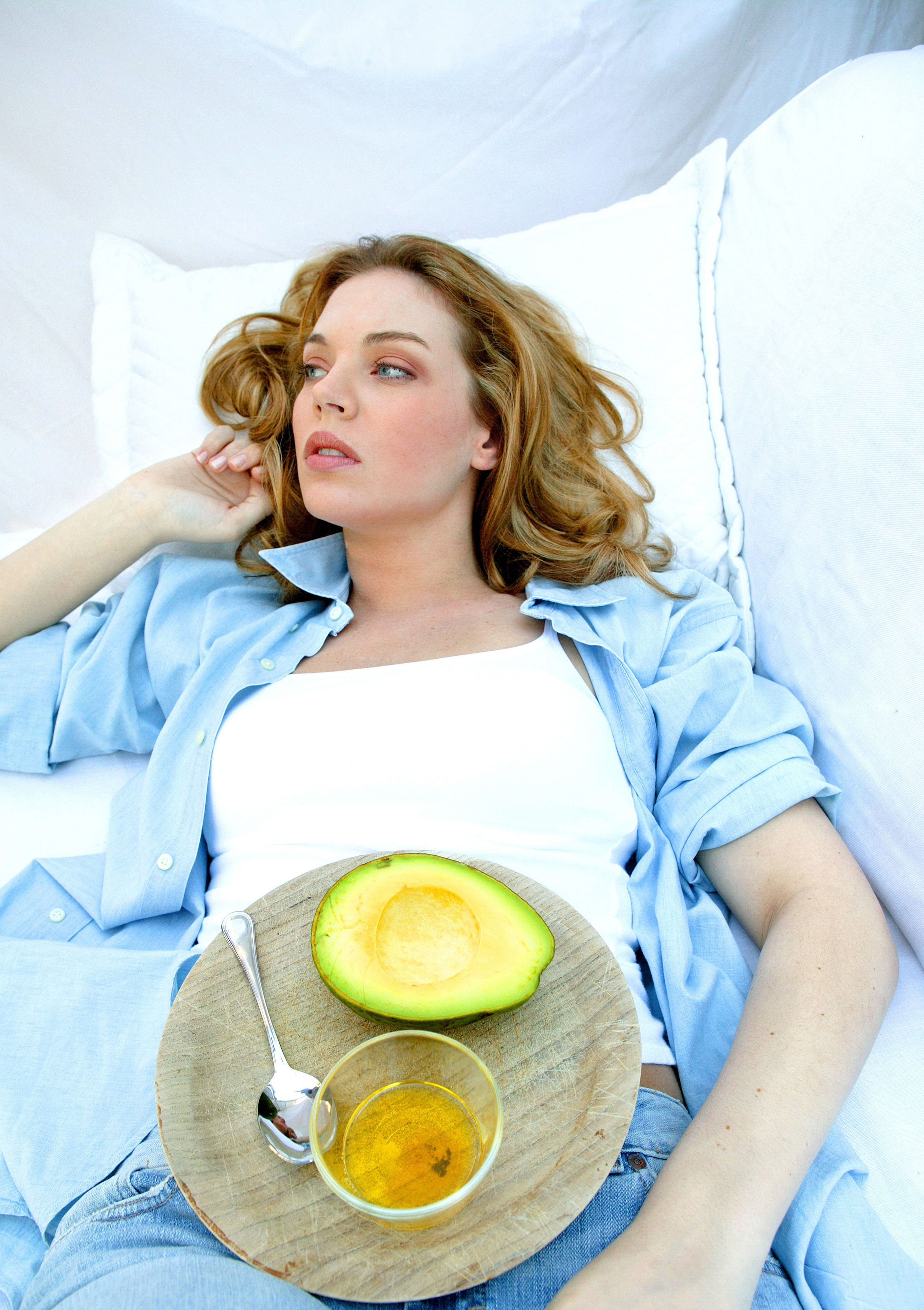 woman lying ob bed with tray on her belly with avocado fruit